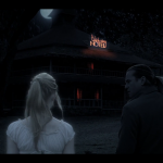 Two people stand in front of a hotel at night